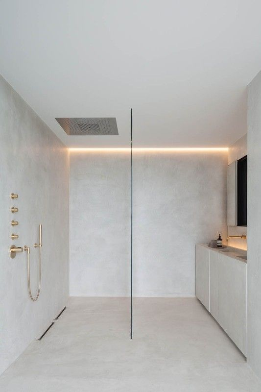 minimalist bathroom design in dominant white flat paneled cabinetry gold bath appliances concealed light fixture on ceilings