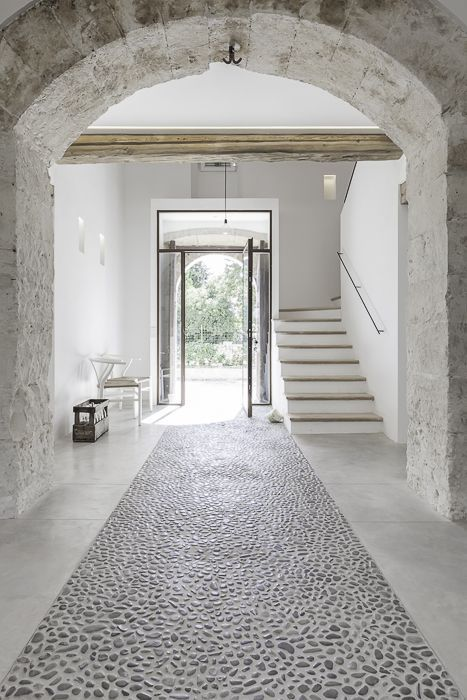 modern entryway with medieval touch whitewashed walls stoned floors clear glass front door modern interior staircase exposed wood beams