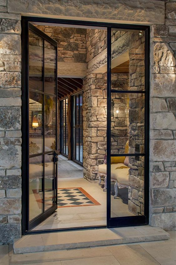modern glass front door with black metal frames and trims stoned exterior walls