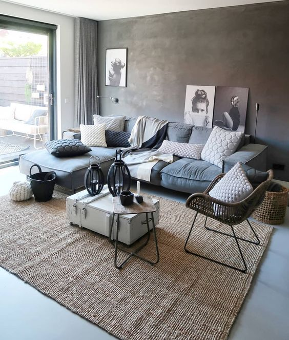 modern living room idea gray walls modern couch in gray white and gray throw pillows suitcase coffee table in white rattan chair with thin metal legs hand knitted area rug