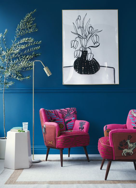 modern seating area deep blue wall painting white black painting with thin frame deep magenta chairs with animal floral prints modern white side table modern floor lamp