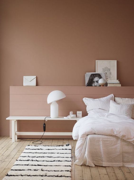 pinky teraccotta colored wall painting whitewashed wood board floors white crisp bedside bench white bedding treatment