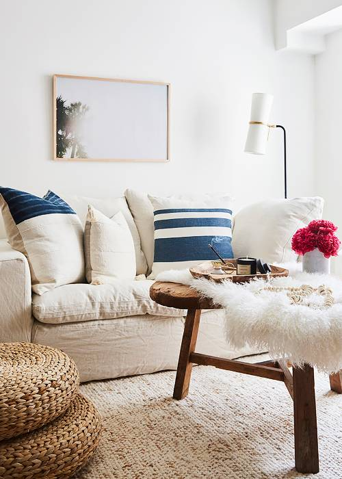 reclaimed heart shaped coffee table with fury white cover woven poufs white sofa with throw pillows textural white area rug