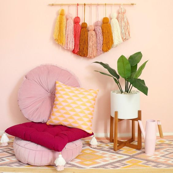 seating area round shaped floor pillows in light purple yellow patterned floor pillow colorful area rug with modern patterns white potted houseplant with wood pot stand colorful hanging art