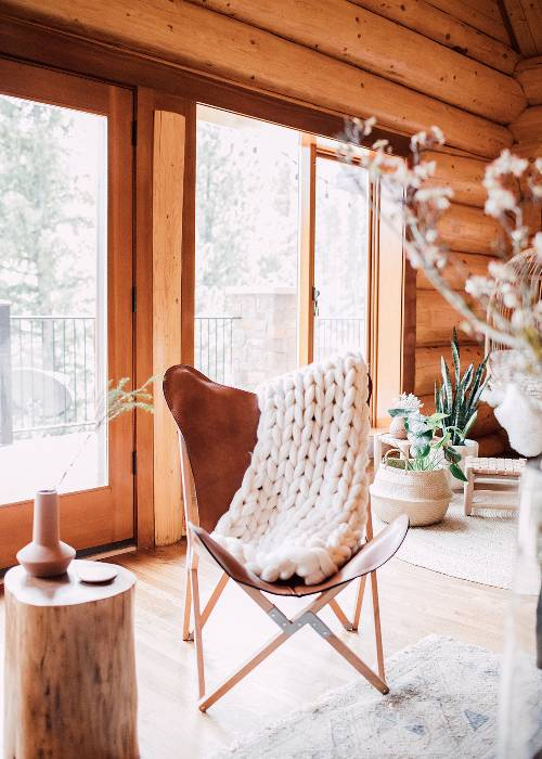small seating idea in log cabin white woven throw blanket log side table