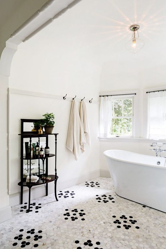 white floors with clustered black dot patterns black table for bath supplies white bathtub glass windows with white curtains black hooks for towels