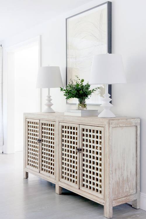 whitewashed storage unit with pored doors a couple of table lamps in white oversize wall art with black frame