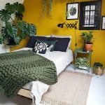 Yellow Wall Small And Medium Houseplants On Pots White Bed Linen Woven Wool Blanket In Green