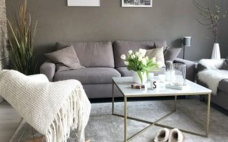 Scandinavian style living room gray wall painting light gray sofa rocking chair with hand knitted throw light gray area rug coffee table with brass legs