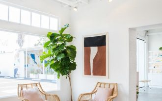 airy eclectic style seating area a couple of rattan chairs with throw pillows light cream area rug with modern patterns potted houseplant exposed wood beams in white concrete floors