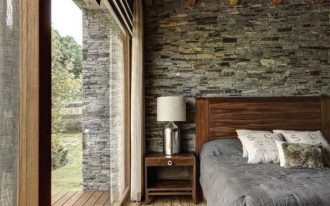 cabin's bedroom idea with clear glass paneled belvederes nearest the bed stoned wall wood board floors exposed wood beams