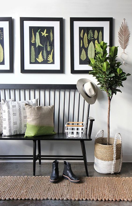 hallway idea black painted wood bench with back some throw pillows woven runner natural fiber woven pot with greenery some black framed ornate pictures