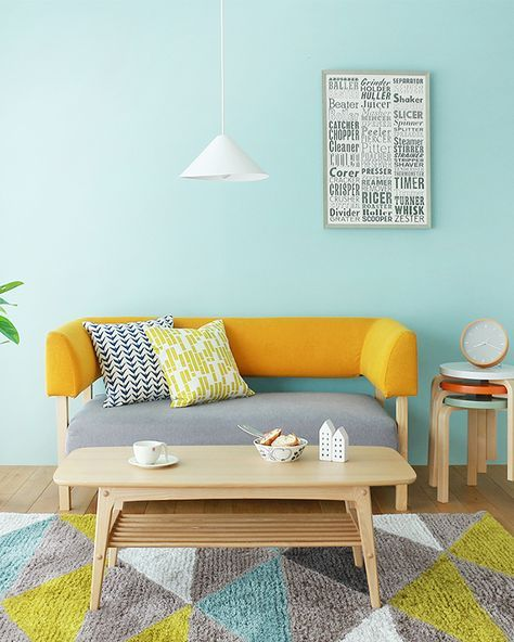 light blue walls modern minimalist couch with pop of yellow and gray light wood coffee table colorful area rug with modern pattern simple white pendant