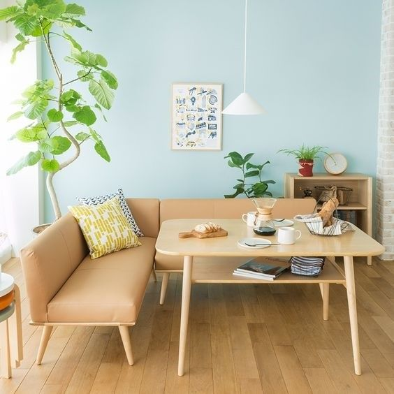 light wood coffee table midcentury modern couch in L shape with wood color like leather finish light wood floors light blue walls medium size houseplant simple white pendant