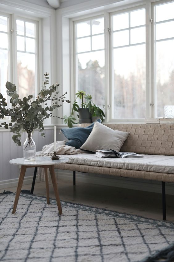 long bench with back feature some throw pillows round top coffee table in midcentury modern style modern patterned area rug
