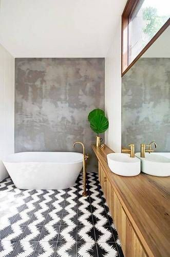 modern bathroom idea monochromatic tile floors with herringbone patterns concrete wall accent little greenery on gold pot white bathtub white sink with gold faucet