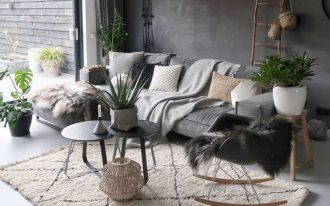 modern living room with Scandinavian touch concrete walls in gray paint white area rug with line accent round top coffee tables in doff black light gray couch rocking chair
