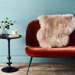 Sheepskin Throw In White Deep Orange Loveseat In Midcentury Modern Style Round Top End Table In Black