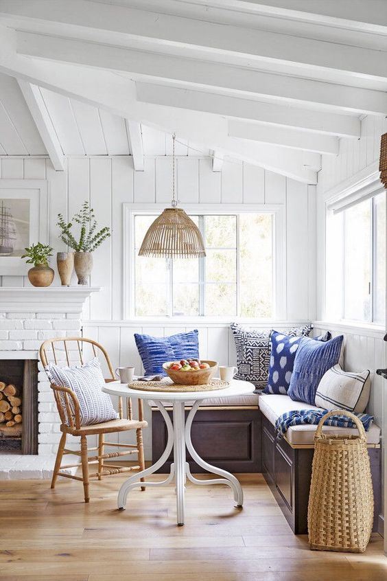 small breakfast nook in farmhouse round top dining table in white loght wood chair L shaped bench seat with lot of throw pillows fireplace with some potted greenery