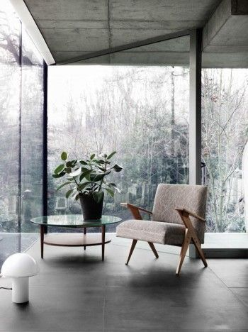 small seating idea in Brut style interior midcentury modern chair round top glass coffee table textured concrete ceilings smooth finished concrete floors full glass window panelings