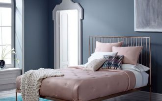 traditional bed frame with rose gold finish metallic structure light pink comforter and pillows white hand knitted wool blanket