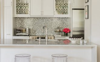 transitional kitchen design two clear acrylic stools white kitchen island mosaic tile backsplash centered upper cabinet clear glass door cabinets
