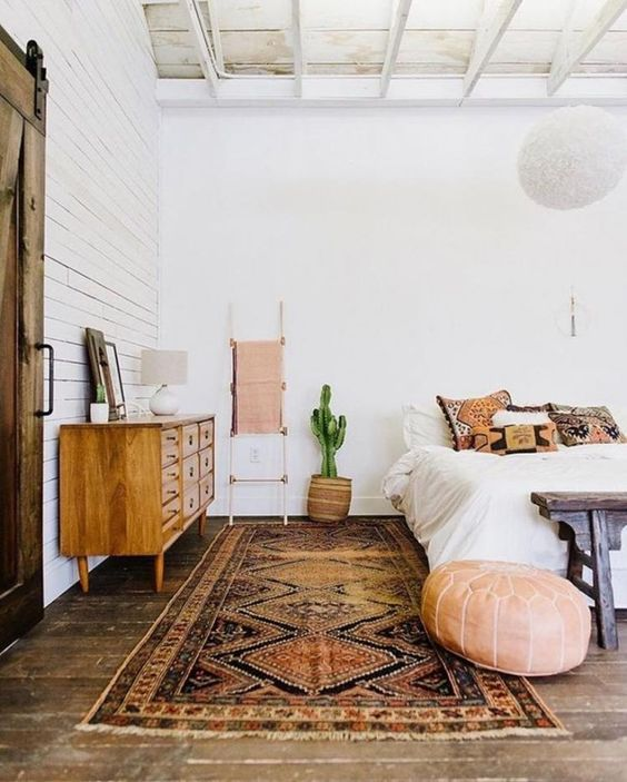 Boho chic bedroom idea crispy white wall painting white bedding idea Boho pillowcases ottoman chair wood bench bed persian rug midcentury modern dresser