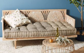Boho style daybed with tufted upholstery and floral carving details cage like coffee table shag rug in white potted plant