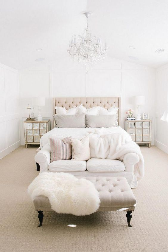 French country bedroom bed frame with tufted headboard white bedding linen white couch with throw pillows tufted coffee table