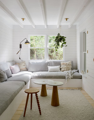 Scandinavian family room L shaped couch in white white throw pillows round top wood tables wooly area rug in broken white tone wood board walls exposed beams