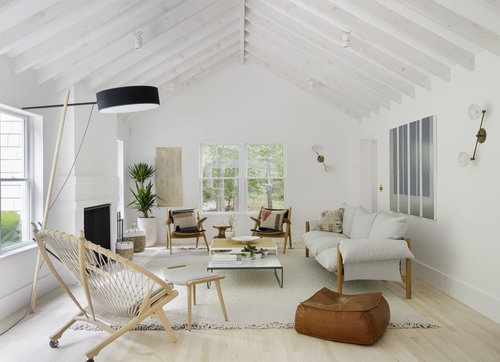 Scandinavian living room exposed wood beams in white white area rug light wood floors light wood furniture set dark brown beanbag floor lamp with black lampshade
