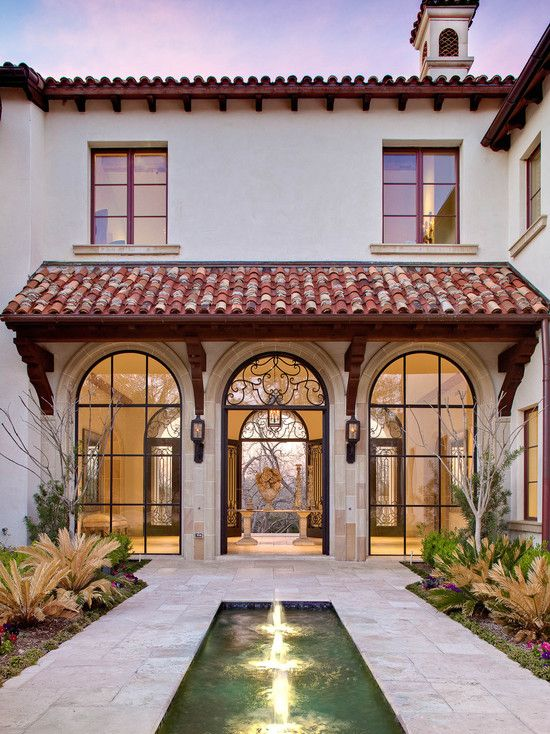 Spanish colonial exterior with flatter roofs curved windows and door
