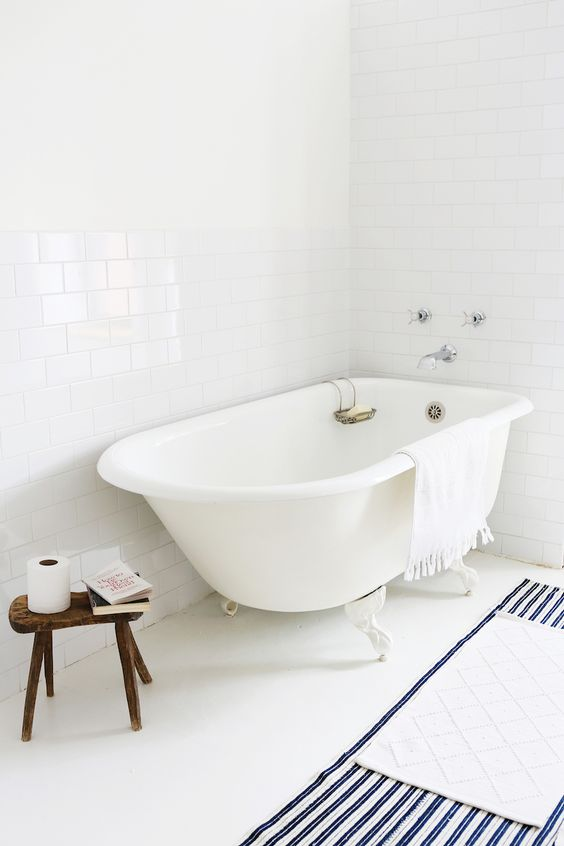 all white modern rustic white clawn feet bathtub striped rug in white deep blue wooden stool white subway tile walls