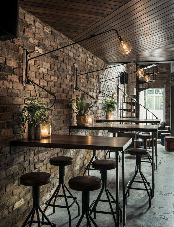 industrial inspired commercial space exposed brick walls wall mounted light fixture in industrial style wall mounted table bar stools concrete floors