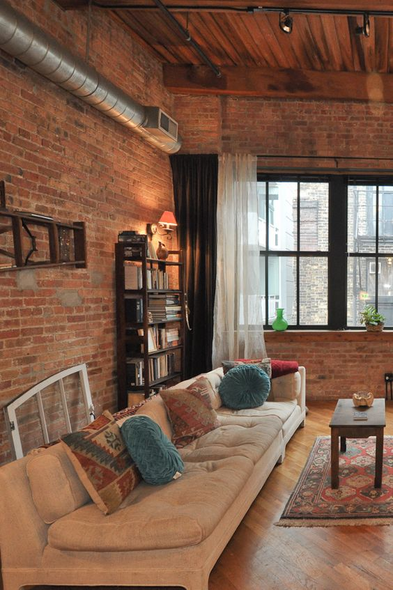 industrial living room design tufted couch in white colorful throw pillows white black draperies exposed brick walls exposed piping installation vintage area rug