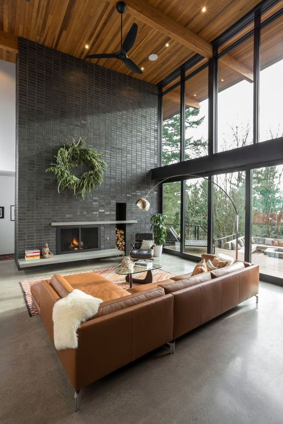 industrial living room idea modern leather couch modern fireplace black brick walls exposed wood beams and ceilings glass windows with black trims