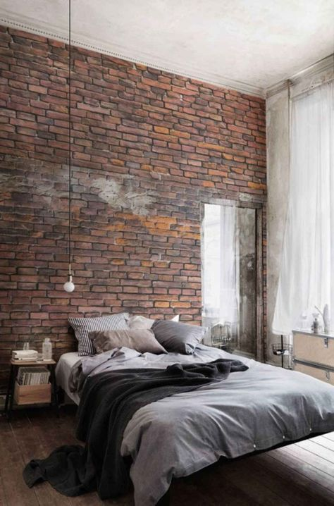 industrial style bedroom exposed brick walls worn wood planked floors large glass windows with semi transparant curtains in white light gray bedding treatment