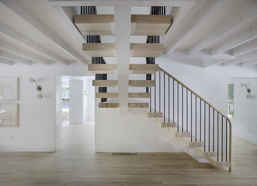 interior staircase with wood steps and concrete central support black finish railings