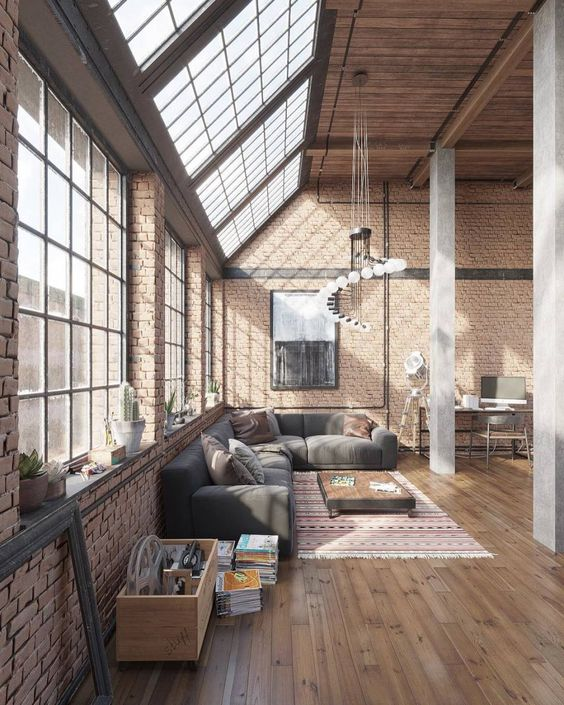 large glass windows with black trims glass skylight wooden ceilings industrial style lighting fixtures dark gray couch with throw pillows low level wood coffee table brick walls wood