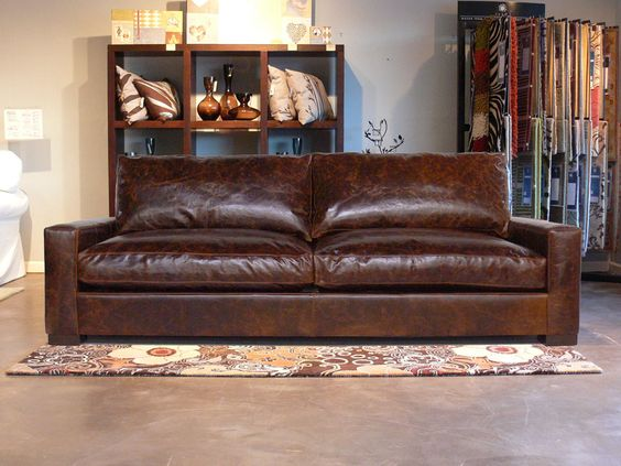 leather couch by Restoration Hardware hardwood shelving unit floral patterned area rug