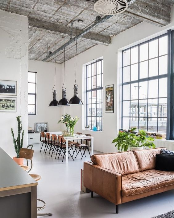 leather couch with black throw pillows industrial style pendants metal base dining chairs white dining table large glass windows whitewashed wood ceilings with exposed wood beams
