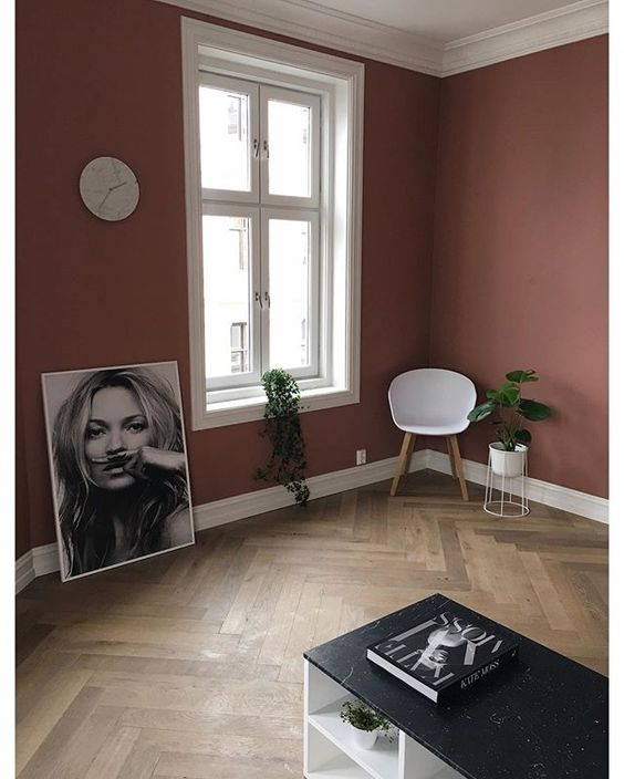 matte pink wall painted white window trims and ceilings herringbone patterned wood floors corner modern chair smaller greenery on pot