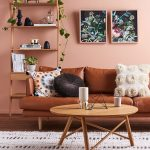 Modern Style Leather Couch With Throw Pillows Round Top Wood Coffee Table In Modern Style Wood Rack Pink Wall Painting Textured Area Rug In White