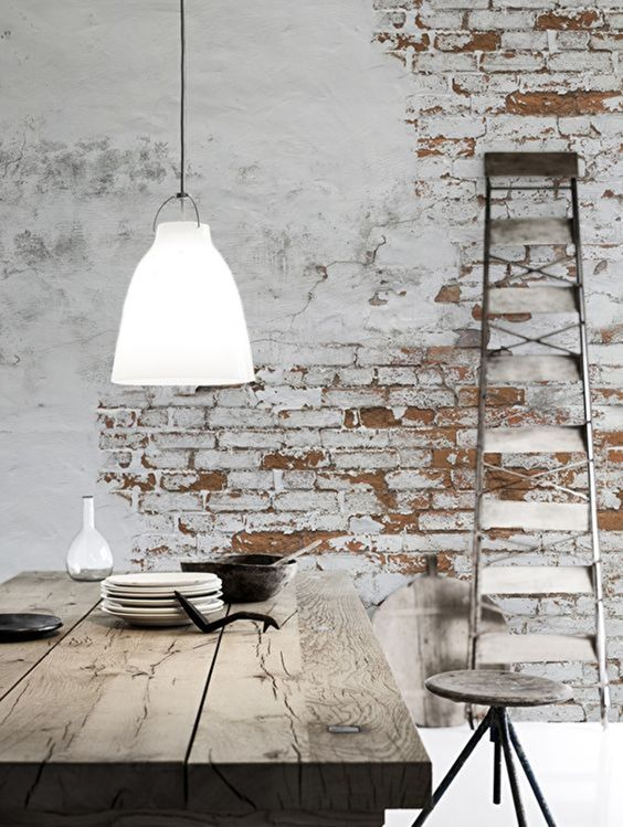 ornate metal ladder washed dining table angled leg stool whitewashed brick walls low level pendant
