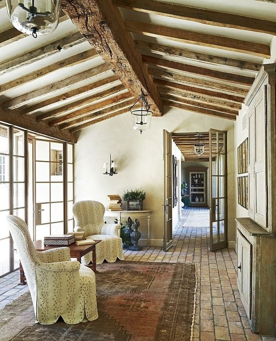 semi rustic French country living room a couple of French chair slipcovers in white wood side table vintage area rug stoned floors exposed wood beams