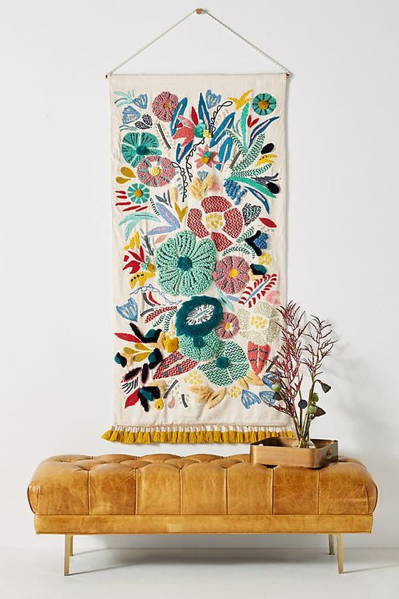 simple Bohemian seating area handmade wall hanging art with hand embroided details tufted bench seat in brown