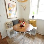 Uncluttered Minimalist Breakfast Nook Idea L Shaped Bench Seat With Under Open Shelves Round Top Wood Dining Table Some Throw Pillows