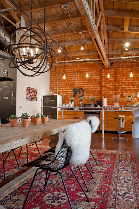 vintage area rug block butcher dining table midcentury modern dining chairs exposed beams and ceilings industrial lighting fixture exposed brick walls