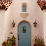 White Painted Stuco Exterior Walls Curved Exterior Door With Light Blue Door Panel Tiny Window With Blue Window Panel Terracotta Floors