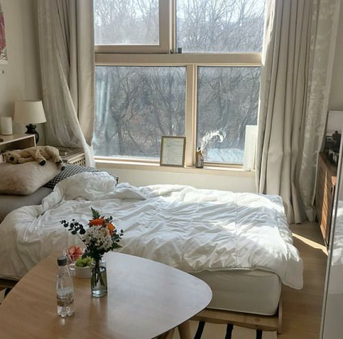90s bedroom in beige beige window curtains white comforter light wood table and bed frame beige wall painting